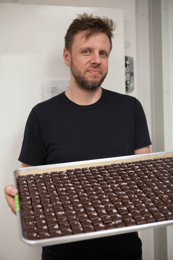 BETA5 Adam Portrait infront of fridge holding tray of choclates